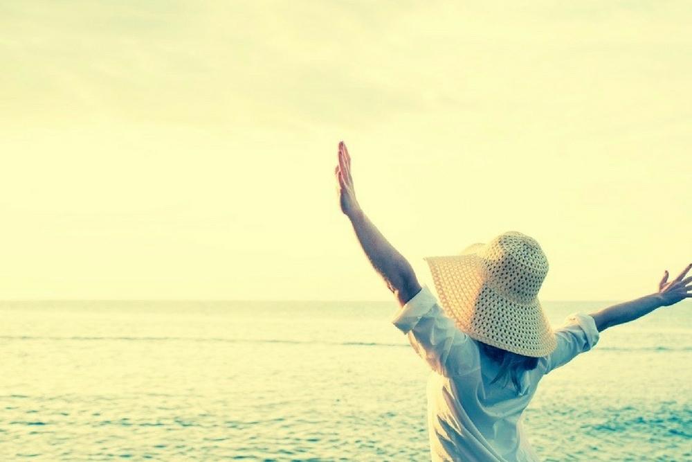 femme a chapeau devant l'ocean