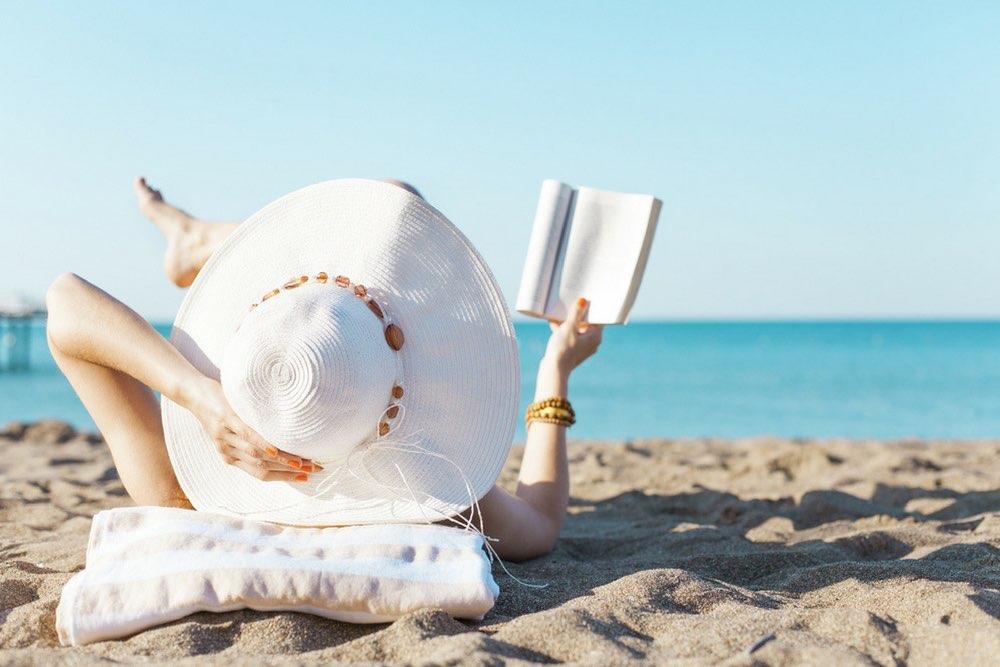 femme a chapeau qui lit a la plage