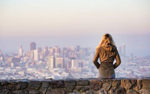 femme assisse pensive devant la ville