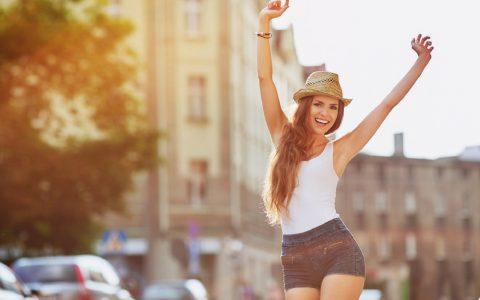 femme heureuse au chapeau en ville